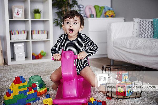 Porträt eines kleinen Jungen  der auf einem rosa Schaukelpferd im Wohnzimmer sitzt.