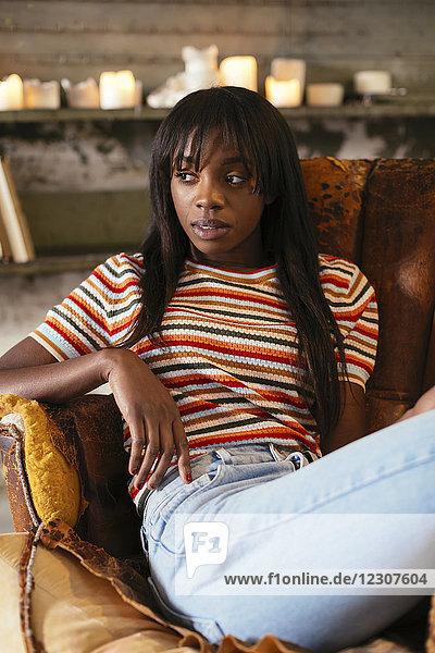 Porträt einer ernsthaften jungen Frau  die auf einem alten Ledersessel in einem Loft sitzt.