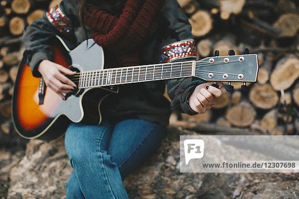 Junge Frau beim Gitarrespielen im Freien  Teilansicht