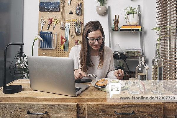Frau beim Mittagessen am Holztisch mit Laptop