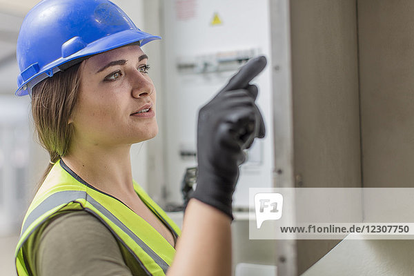 Young female electrician working at fusebox