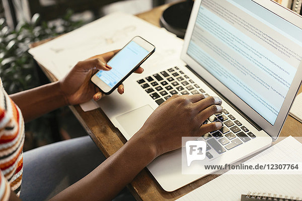 Frau sitzt am Schreibtisch mit Smartphone und Laptop  Teilansicht