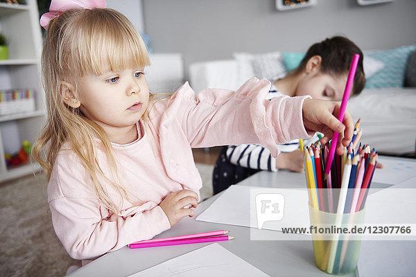 Porträt des kleinen Mädchens mit Buntstiften im Wohnzimmer