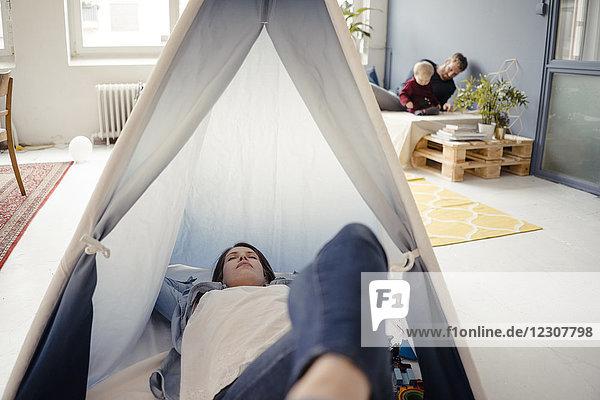 Frau ruht im Zelt  während Vater mit ihrem Sohn im Hintergrund spielt.
