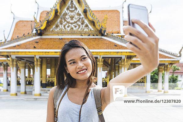 Thailand,  Bangkok,  Porträt eines lächelnden Touristen,  der sich selbst mit dem Smartphone fotografiert.