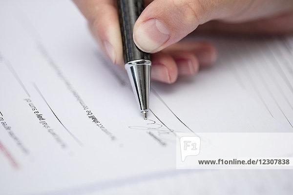 Frau beim Unterschreiben von Dokumenten