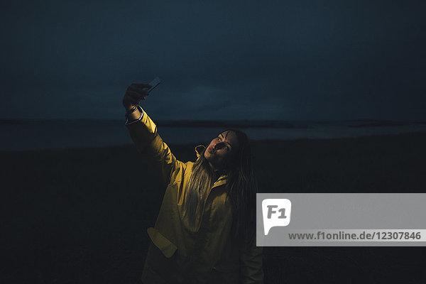 Frankreich  Bretagne  Landeda  Dunes de Sainte-Marguerite  Frau mit einem Selfie am Strand bei Nacht