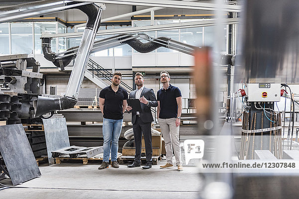 Three men standing and talking on factory shop floor