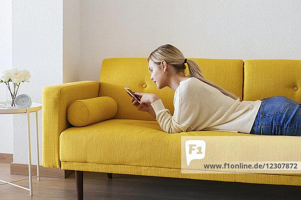 Blonde Frau auf dem Sofa liegend  mit Smartphone zu Hause