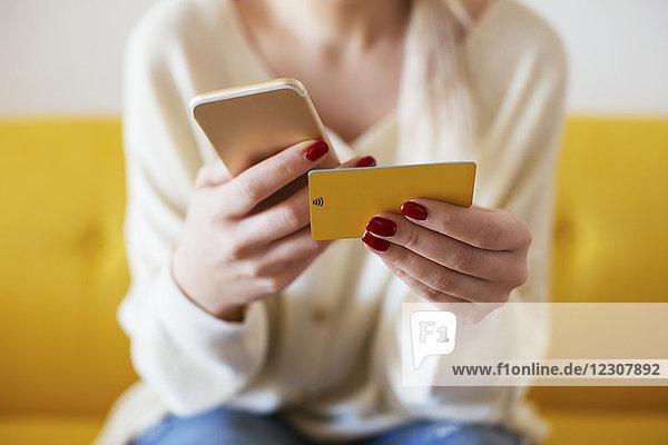 Blonde Frau mit Smartphone und Bankkarte zu Hause