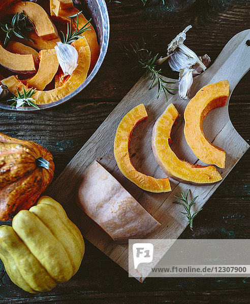 Pumpkin slices  garlic and rosemary on wooden board and in casserolle
