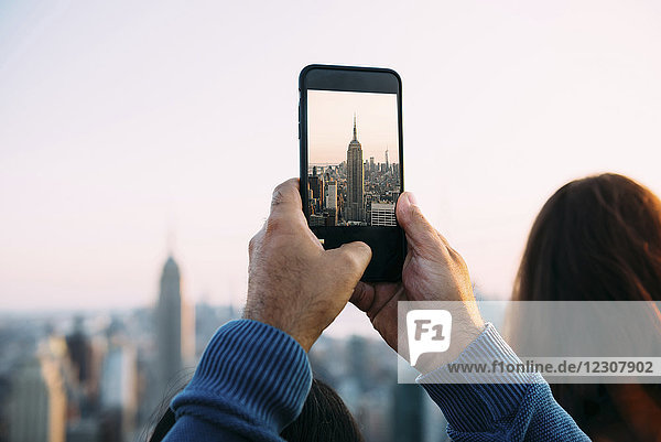 USA  New York City  man's hands taking a photo of Empire State Building with smartphone