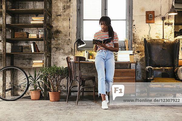 Junge Frau steht vor dem Schreibtisch in einem Loft mit Notizbuch