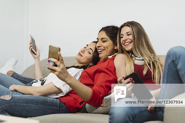 Fröhliche junge Frauen im Büro mit dem Handy
