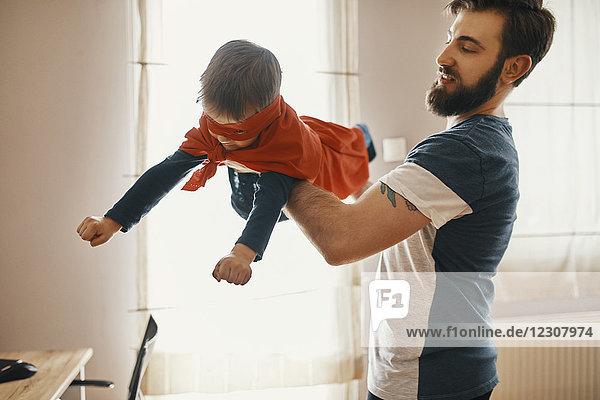 Vater spielt mit seinem kleinen Sohn  verkleidet als Superheld.