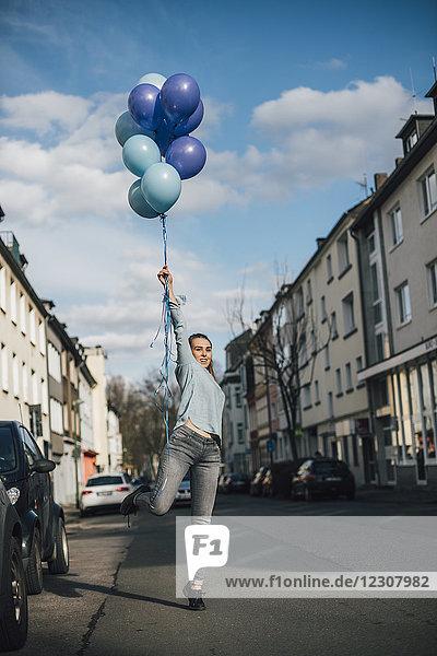 Lächelnde Frau mit blauen Luftballons auf der Straße