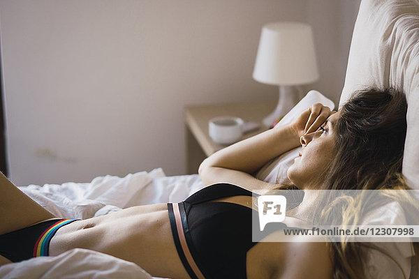 Tagträumende junge Frau in Unterwäsche auf dem Bett liegend