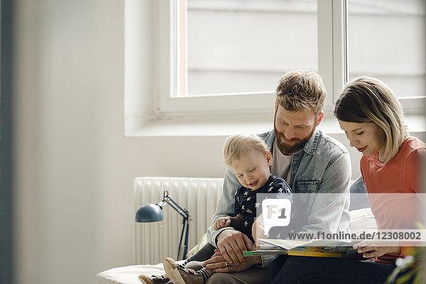 Kleiner Junge sitzt auf Vaters Schoß  Mutter liest Kinderbuch vor