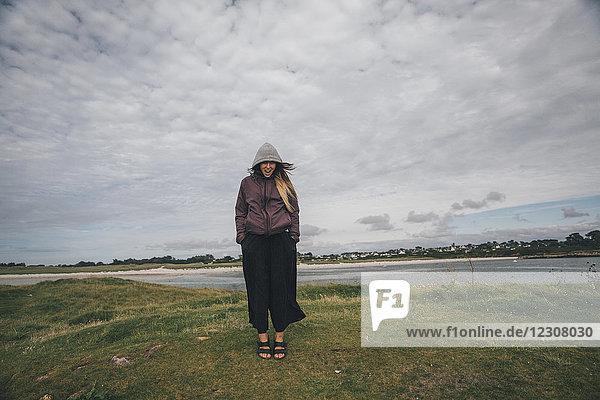 Frankreich,  Bretagne,  Landeda,  Dunes de Sainte-Marguerite,  junge Frau an der Küste stehend