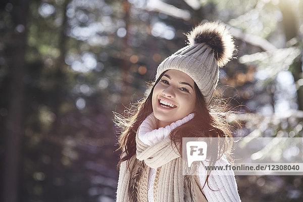 Porträt einer lachenden jungen Frau in Strickwaren im Winterwald