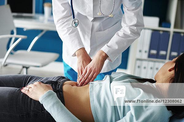 Arzt untersucht den Magen der Frau in der Arztpraxis