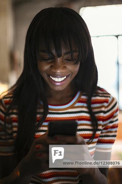 Porträt einer glücklichen jungen Frau beim Blick aufs Handy