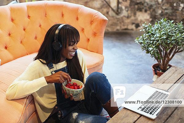 Lachende junge Frau  die mit Laptop und Kopfhörer auf dem Boden ihres Loftes sitzt.