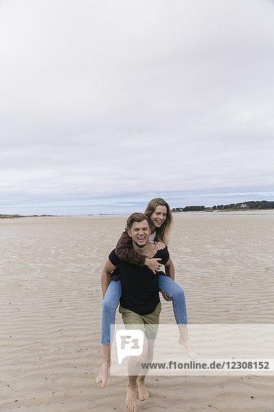 Frankreich  Bretagne  Guisseny  glücklicher junger Mann mit Freundin Huckepack am Strand