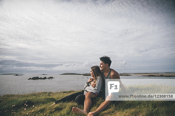 Frankreich  Bretagne  Landeda  Dunes de Sainte-Marguerite  liebevolles junges Paar an der Küste sitzend