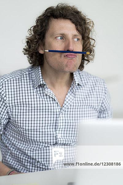 Geschäftsmann mit Bleistift im Gesicht