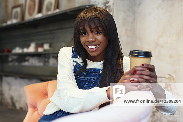 Portrait of smiling woman with coffee to go sitting on the couch in a loft