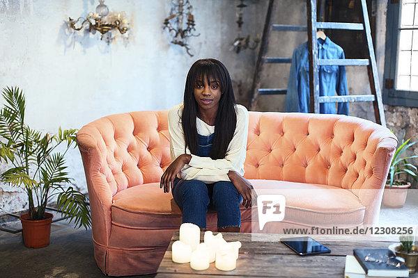 Porträt einer jungen Frau  die auf der Couch in ihrem Loft sitzt.