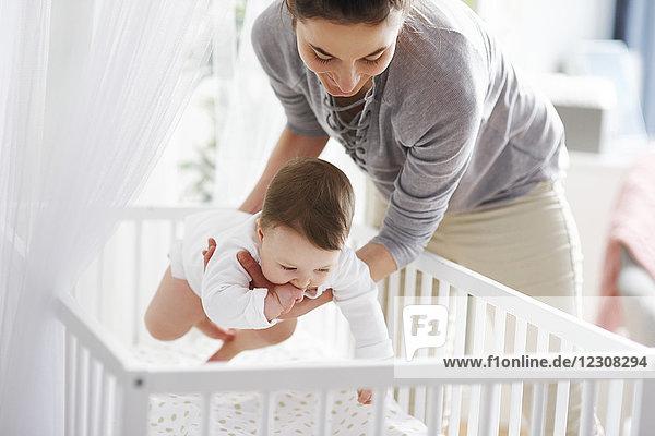 Mutter legt ihr Baby zu Hause in die Krippe