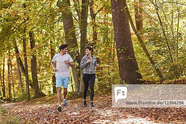Paarjogging auf herbstlichem Waldweg