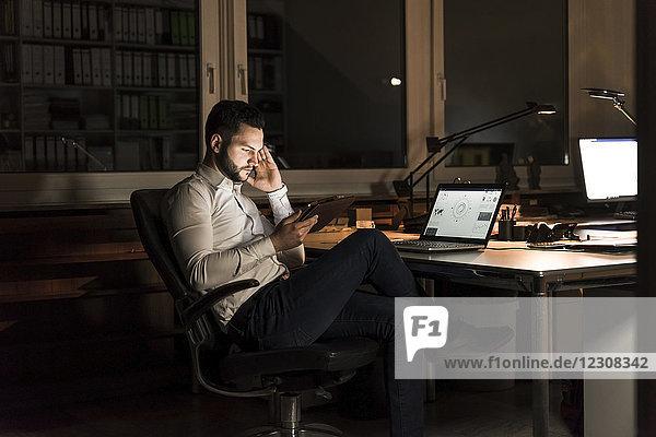 Geschäftsmann mit Tablette im Büro bei Nacht