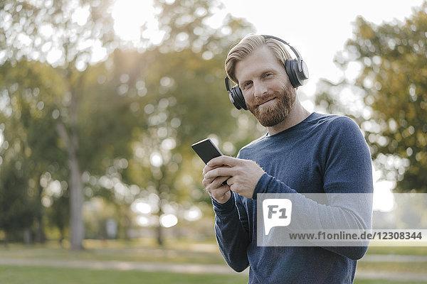 Porträt eines lächelnden Mannes mit Handy beim Musikhören mit Kopfhörern im Park