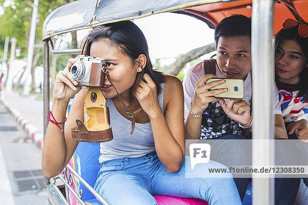 Thailand,  Bangkok,  drei Freunde auf Tuk Tuk Tuk beim Fotografieren mit dem Smartphone