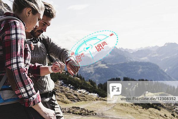 Junges Paar macht Pause vom Wandern und überprüft die Daten von smartwatch