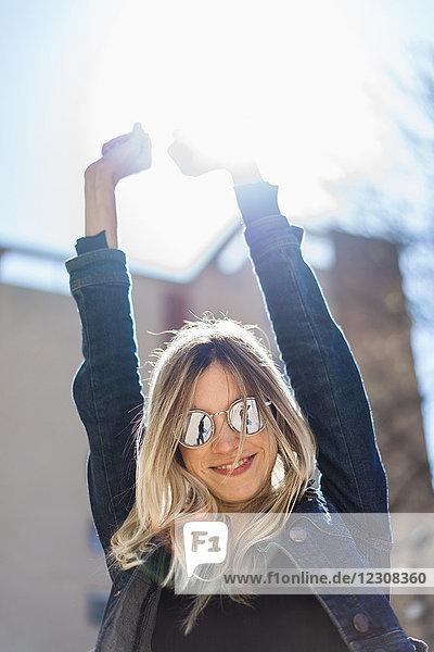 Porträt einer glücklichen jungen Frau mit verspiegelter Sonnenbrille