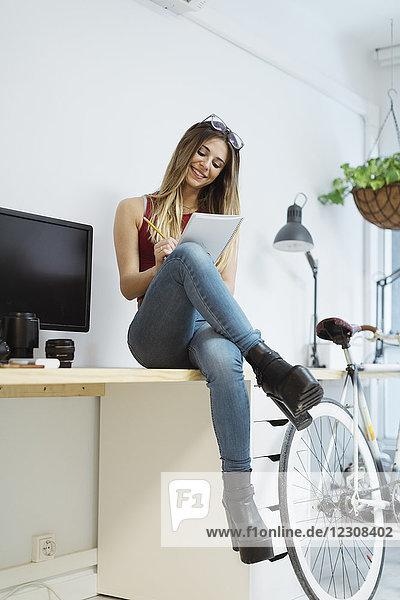 Lächelnde junge Frau sitzt auf dem Schreibtisch im Büro und macht sich Notizen.