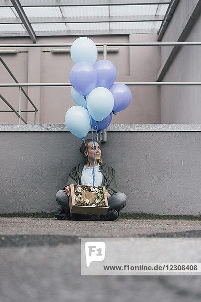 Lächelnde Frau mit Blumen in Pappschachtel und blauen Luftballons auf dem Boden sitzend