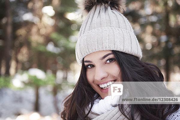 Porträt einer lächelnden jungen Frau mit Wollmütze im Wald