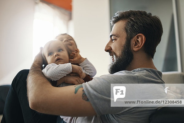 Happy father with baby girl and little son together at home