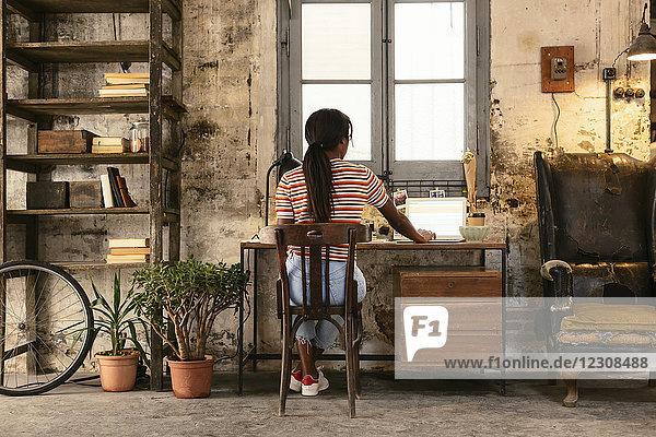 Rückansicht einer jungen Frau  die am Schreibtisch in einem Loft sitzt und am Laptop arbeitet.