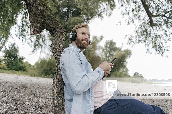 Deutschland  Düsseldorf  Mann beim Musikhören mit Smartphone und Kopfhörer am Strand