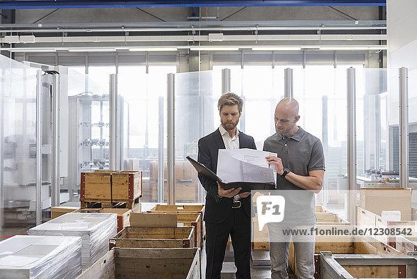 Geschäftsmann und Angestellter beim Betrachten des Plans in der Fabrikhalle