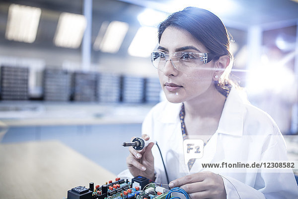 Female technician working on motherboard