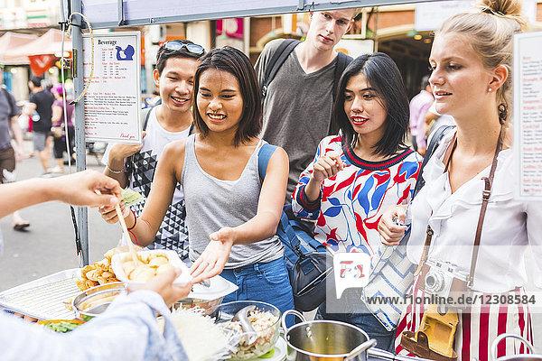Thailand  Bangkok  Khao San Road  Gruppe von Freunden  die lokale Lebensmittel auf dem Straßenmarkt testen.
