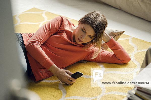 Frau mit Smartphone zu Hause
