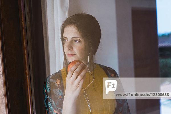Junge Frau mit Kopfhörer und Apfel aus dem Fenster schauend Junge Frau mit Kopfhörer und Apfel aus dem Fenster schauend